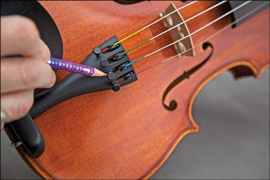 Usando um lápis macio para ajudar os sintonizadores finos virar suavemente. [Fotografia por Nathan Saliwonchy